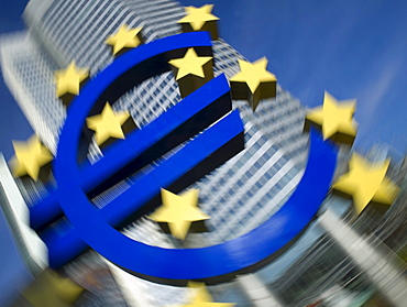 Symbol of the euro currency, the European Central Bank behind, ECB, Euro Tower, motion blur, Frankfurt am Main, Hesse, Germany, Europe