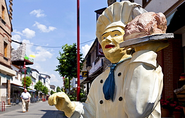 Chef holding a roast, advertising character outside a restaurant