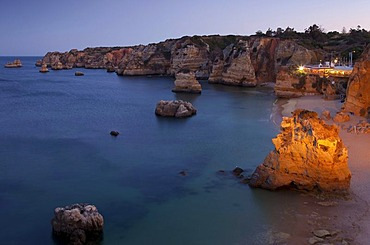 Rugged rocky coastline with illuminated restaurant in the evening light, Lagos, Algarve, Portugal, Europe