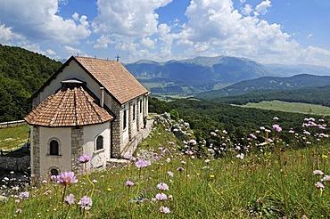 Hikers at the church Santa Maria di Monte Tranquillo, Villetta Barrea, National Park of Abruzzo, Italy, Europe