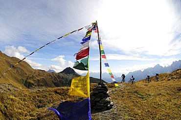 Mountain bikers in front of prayer flags, on the Carnian trail, Mt. Helm, Alta Pusteria, South Tyrol, Dolomites, Italy, Europe