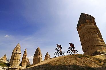 Mountain bikers cycling in Love Valley, Guevercinlik Valley, Goereme, Cappadocia, Turkey