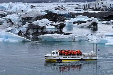 Boat tour passing icebergs in the Joekulsarlon glacial lake, Iceland, Europe