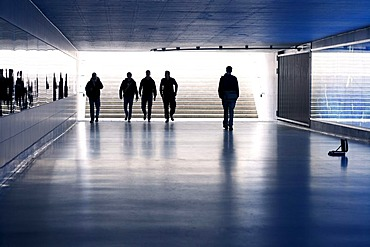 Man approaching a group of menacing-looking youths in a dark pedestrian underpass