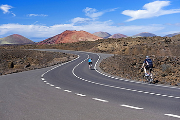 Cyclists on a road, volcanic landscape at Los Hervideros, Timanfaya National Park, Lanzarote, Canary Islands, Spain, Europe