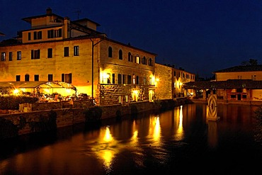 The basin of hot sulphur spring in Bagno Vignoni and Hotel Le Terme at night, Orcia Valley, Tuscany, Italy, Europe