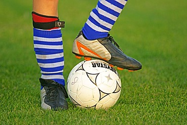 Detail of a soccer player's legs with foot on a football, shoes, football cosk