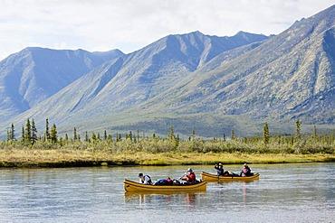 Canoeists on the Wind River, canoeing, paddling a canoe, Northern Mackenzie Mountains behind, Yukon Territory, Canada