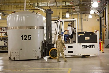Workers prepare transuranic nuclear waste from America's nuclear weapons program for long-term storage at the Waste Isolation Pilot Plant, here a fork lift moves a TRUPACT shipping container used to transport nuclear waste by truck from distant places.; t