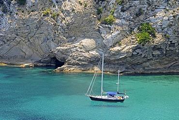 Single sailing boat, bay, rocky coast, Punta Grossa, Cala de San Vicente bay, Ibiza island, Pityuses, Balearic Islands, Spain, Europe