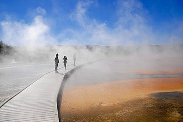 People on a cordwood bridgeway at the Grand Prismatic Spring, Midway Geyser Basin, Yellowstone National Park, Wyoming, USA