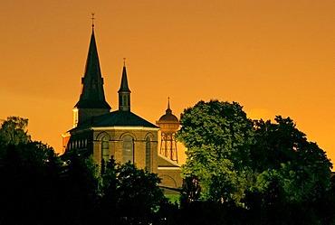 Parish church and water tower with sky lit by Duisburg steel works, Lank-Latum, Meerbusch, North Rhine-Westfalia, Germany, Europe