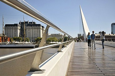 Tourists walking on a modern suspension bridge, Puente de la Mujer bridge, Women's Bridge, in the old harbor of Puerto Madero, Buenos Aires, Argentina, South America