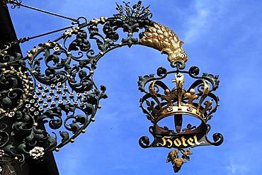 Ornamental wrought-iron inn sign, crown, against a blue sky, Breisacherstrasse 1, Neuenburg am Rhein, Baden-Wuerttemberg, Germany, Europe