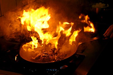 Explosive flame in a frying pan with fried meat on a gas stove with fat which is too hot