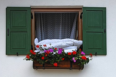 Duvets hanging out of a window with flower box for airing, Mittenwald, Upper Bavaria, Bavaria, Germany, Europe