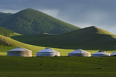 Rain clouds over a yurt camp or ger camp, grasslands on the Orkhon waterfall in front of the mountains of the Khangai Nuur National Park Orkhon Khuerkhree, Kharkhorin, Oevoerkhangai Aimak, Mongolia, Asia