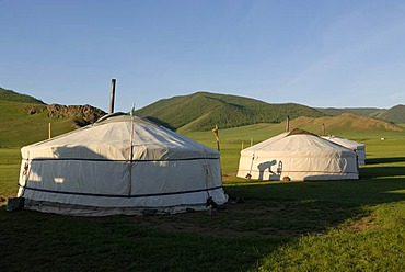 Yurt camp or ger camp in the grasslands at the Orkhon Waterfall in front of the mountains of the Khuisiin Naiman Nuur Nature Reserve, Orkhon Khuerkhree, Kharkhorin, Oevoerkhangai Aimak, Mongolia, Asia