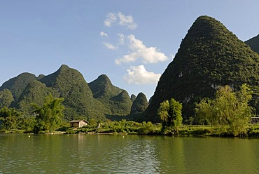 Karst rocks at the Yulong river with bamboo and wooden fishing hut in Yangshuo, Guilin, Guangxi, China, Asia