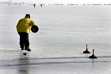 Bavarian game of Eisstock, ice stock, on frozen lake Chiemsee, Chiemgau, Upper Bavaria, Germany, Europe