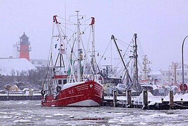 Fishing boats in the frozen harbour of Buesum in winter with snow on the North Sea coast, lighthouse in the distance, Dithmarschen district, Schleswig-Holstein, Germany, Europe