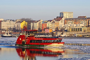 A harbor ferry on the wintery Elbe river in Hamburg's port, Landungsbruecken jetties, Hamburg, Germany, Europe