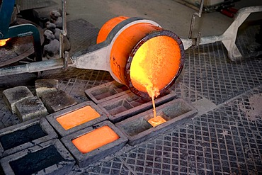 Bronze being poured into moulds, workers in an art foundry