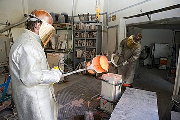 Working in an art foundry, liquid bronze being poured into moulds