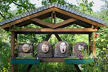 Bee hive, the entry hole for the bees is the mouth of a carved face, left a caricature of George Bush