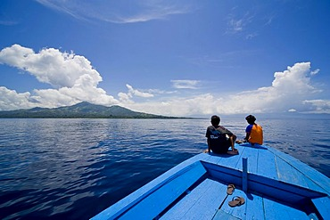 Young couple sitting at the bow of a wooden boat, Siladen island, Sulawesi, Indonesia, Southeast Asia