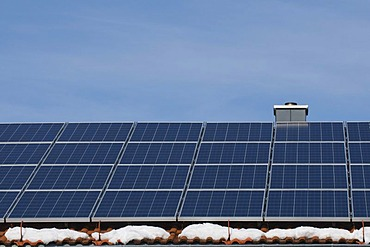 Solar panels on the roof of a house with patches of snow, renewable energy