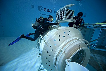 A module of a space station reproduction in a diving basin, backup divers carefully examine the space station, European Space Agency, ESA, European Astronaut Center, EAC, Cologne, North Rhine-Westphalia, Germany, Europe