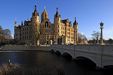 Schwerin Castle and Schlossbruecke bridge against a blue sky behind the frozen Schwerin Lake, the castle was built between 1845 and 1857 during romantic historicism, Lennestrasse 1, Schwerin, Mecklenburg-Western Pomerania, Germany, Europe