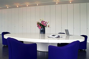 Oval conference table with a laptop and chairs in a modern design in front of a white office wall unit