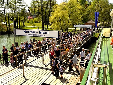 Tourists leaving and waiting to board a ferry boat at Herreninsel island, Chiemgau, Upper Bavaria, Germany, Europe