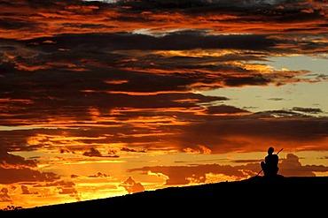Australian Aboriginal sitting on a hill looking into sunset sky, Northwest Australia