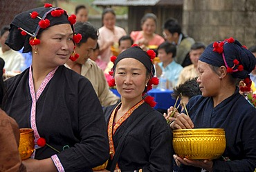Pi Mai, Lao New Year, Women of the Phunoy ethnic group, traditional dress in black with red pompoms, Phongsali city, Laos, Southeast Asia, Asia