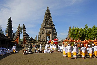 Balinese Hinduism, gathering of believers, ceremony, believers in bright temple dress carrying colourful parasols and shrines, temple tower and in the back the split gate, Candi bentar, Pura Ulun Danu Batur temple, Batur village, Bali, Indonesia, Southeas