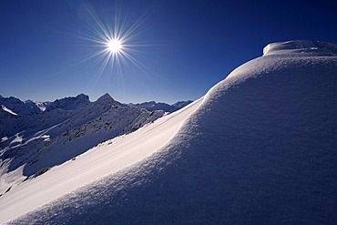 Snow cornice with a star-shaped sun in front of a mountain panorama, Rietzler, Kleinwalsertal, Vorarlberg, Austria, Europe