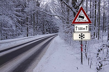 Warning signs in winter, road signs warning of danger of skidding on black ice, and snow on icy road in the forest, Tangstedt, Schleswig-Holstein, Germany, Europe