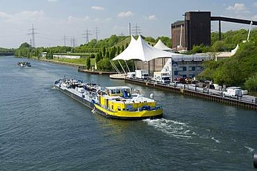 Amphitheater and cargo ship on the Rhine-Herne Canal, Nordsternpark, Route der Industriekultur Route of Industrial Heritage, Gelsenkirchen, Ruhrgebiet region, North Rhine-Westphalia, Germany, Europe