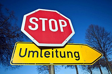 Stop sign and German diversion sign against a blue sky