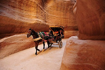 Coach with tourists in the Siq, the one kilometer long canyon that leads to the Nabataean city Petra, Unesco World Heritage Site, near Wadi Musa, Jordan, Middle East, Orient