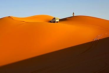 Off-road vehicle driving towards the sunset in the sand dunes of the Erg Muzuruq, Sahara, Libya, Africa