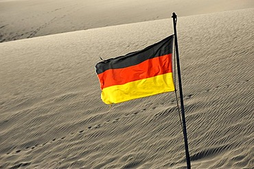 German flag blowing in the desert sand