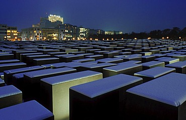 Holocaust Memorial in the snow, memorial to the murdered Jews of Europe, at dusk in winter, with the skyline of Potsdamer Platz square, Tiergarten district, Berlin, Germany, Europe