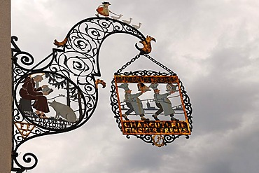 """Ornate iron hanging sign of a slaughterhouse """"CHARCUTERIE FINCK FRERES"""" against a rainy sky, Colmar, Alsace, France, Europe"""