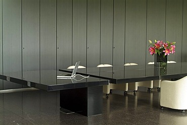 Detailed view of an exclusive black shiny conference table with empty white leather chairs