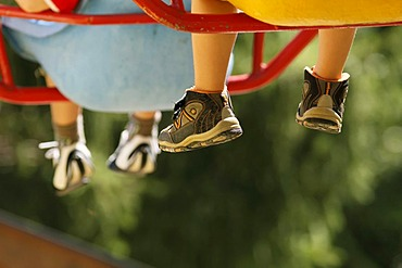 Children's legs and feet on a chair ride