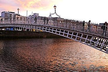People crossing Halpenny Bridge over the Liffey River, Dublin, Ireland, Europe